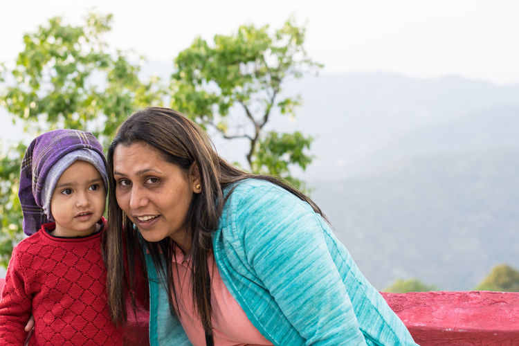 Portrait of mother with daughter against mountain
