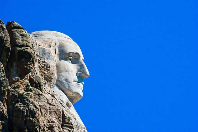 Low Angle View Of Mount Rushmore Against Blue Sky