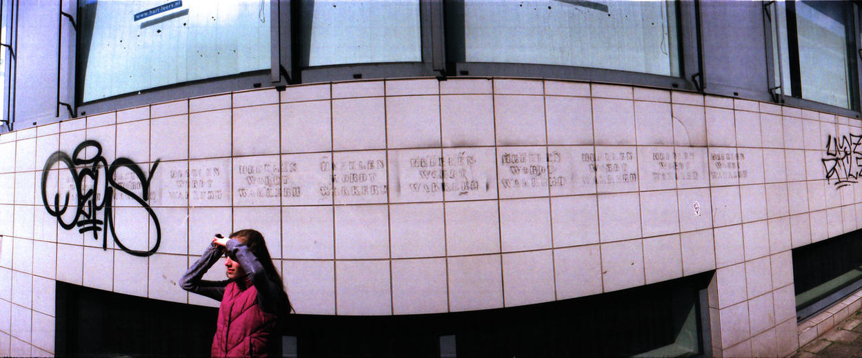 Panoramic View Of Girl Standing By Building