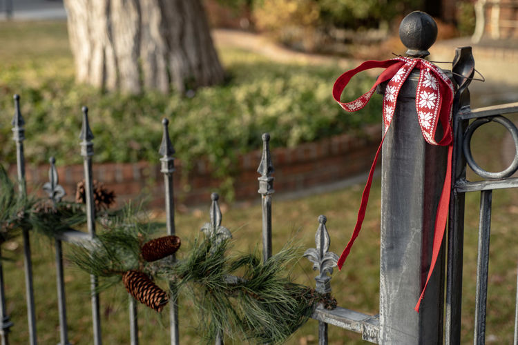 Red ribbon green garland decorations hanging along vintage wrought iron fence