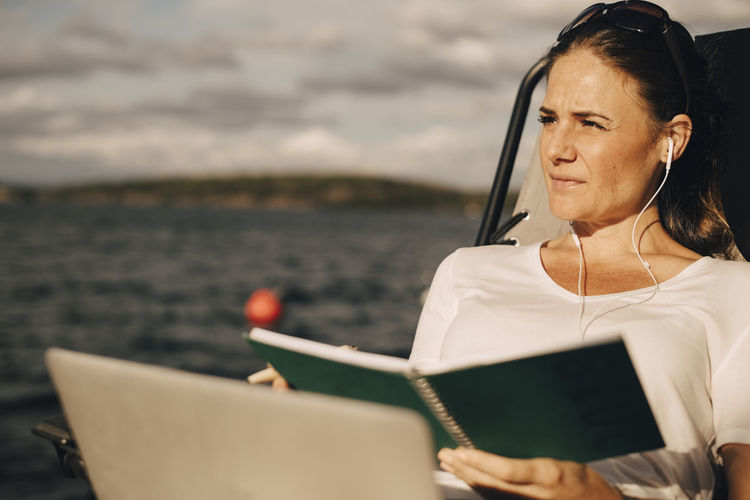Woman looking at camera while sitting by sea