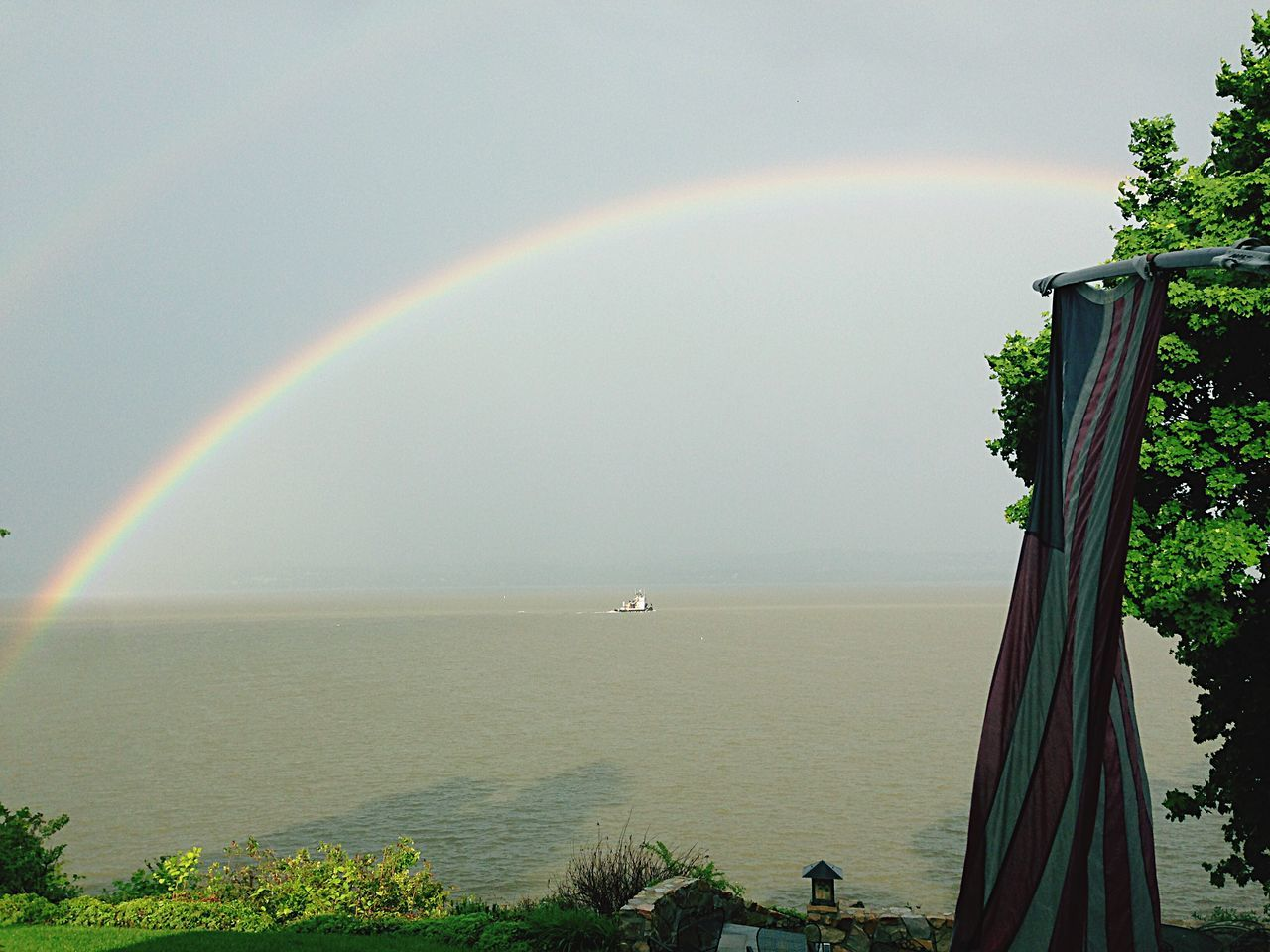 rainbow, nature, beauty in nature, scenics, double rainbow, water, day, sea, tranquil scene, tranquility, outdoors, idyllic, no people, horizon over water, tree, sky, architecture, grass