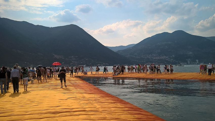 Beauty In Nature Cloud - Sky Day Floating Piers Group Of People Large Group Of People Leisure Activity Lifestyles Medium Group Of People Mixed Age Range Mountain Mountain Range Nature Outdoors Scenics Sky The Way Forward Tourism Tourist Tranquil Scene Tranquility Travel Destinations Unrecognizable Person Vacations Water