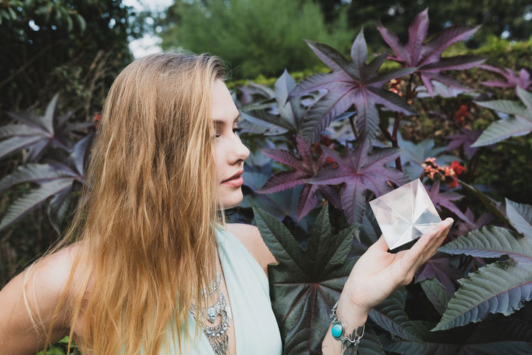 Young woman looking at prism while standing against plant