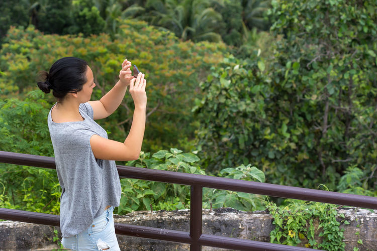 A young woman taking photos of an unknown view with a forest back ground. Adult Black Hair Cheerful Day Forest Freshness Full Length Happiness Healthy Lifestyle Jungle Nature One Person One Young Woman Only Outdoors People Photography Ponytail Side View Smart Phone Standing Taking Photos Tourist Tranquility Travel Viewing