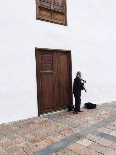 Full length of man playing violin on sidewalk