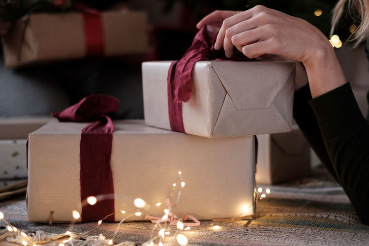 Female hands wrapping christmas gift Gift Low Angle View Focus On Foreground Illuminated Decoration Ribbon - Sewing Item Christmas Present Box - Container Container Box Candle Gift Box Celebration Year Of The Pig Human Body Part X-mas Indoors  Christmas Lights Hand Event Real People Holiday Cozy Wrapping Paper Wrapping Presents Holiday Moments