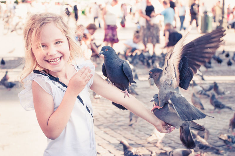 Smiling girl with pigeons on the arm Bird Cheerful Child Childhood CracowCity Crowd Day Fun Happiness Joy Man One Girl Only One Person Outdoors Pigeon Playful Poland Portrait Smile Smiling