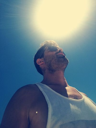Low angel view of man against sky during sunny day