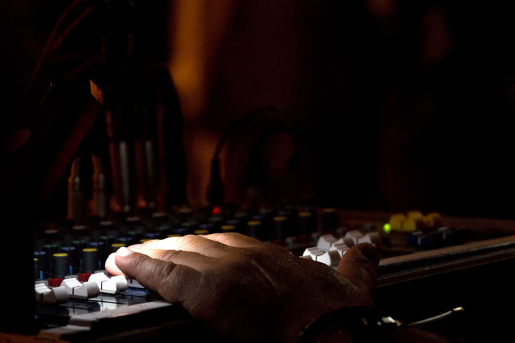 Cropped hand of dj using sound mixer in darkroom