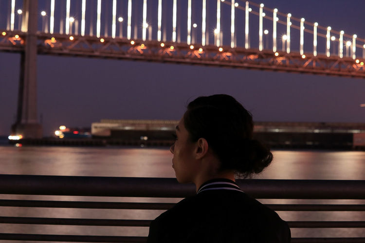 Rear view of woman by river at night