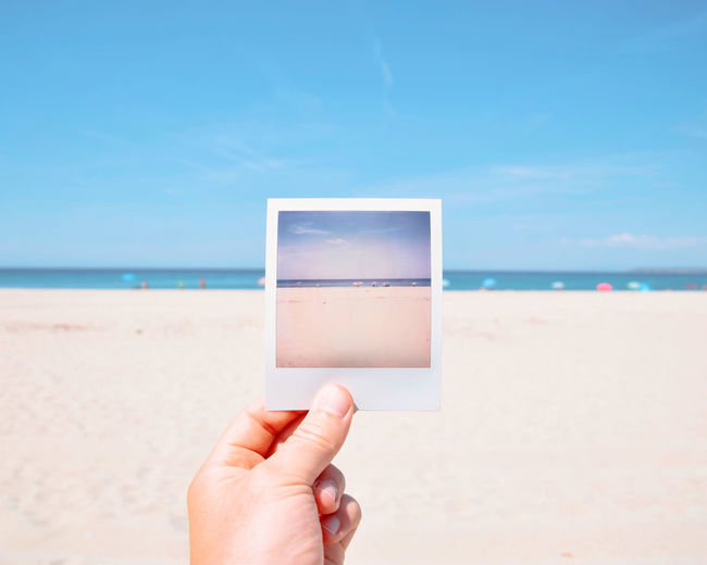 Cropped hand holding instant transfer print at beach