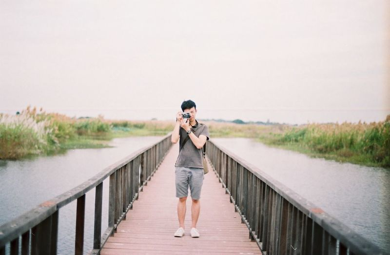 Full Length Of Photographer Photographing On Footbridge Over River Against Clear Sky