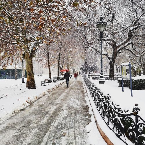 People on snow covered footpath in city