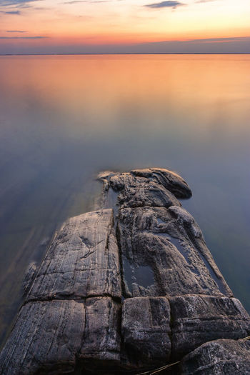 Cliffs at the water edge with flat water at sunset