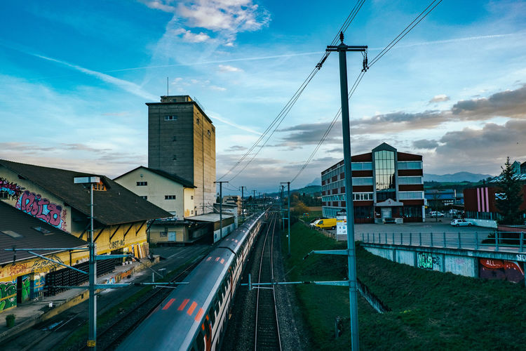High Angle View Of Train With Buildings Against Sky