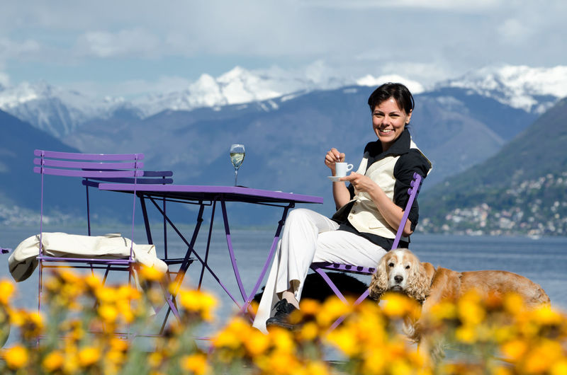 Portrait Of Happy Woman With Dog At Outdoor Cafe