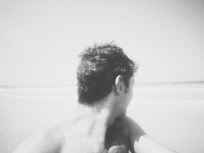 Rear view of shirtless man at beach against sky
