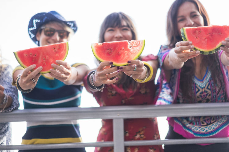 High angle view of friends holding watermelon slices while standing against sky