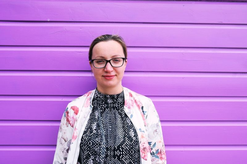 Portrait Of Woman Standing Against Purple Wall