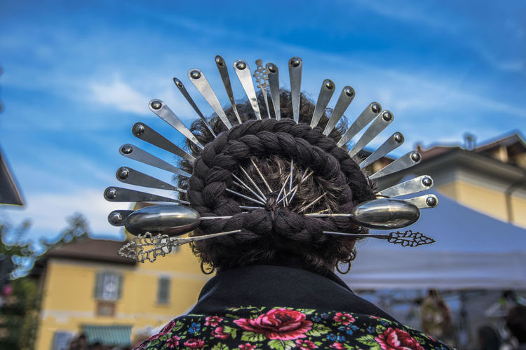 Rear view of woman with decorated spoons and braided hair against sky