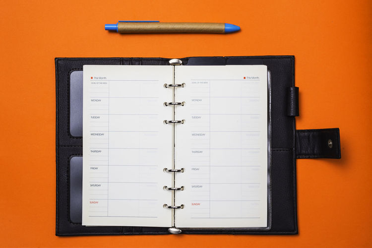 Still Life Indoors  No People Orange Color Paper Close-up Directly Above Pen Communication Table Technology Studio Shot Note Pad Office Orange Background Writing Instrument High Angle View Equipment Office Supply Colored Background