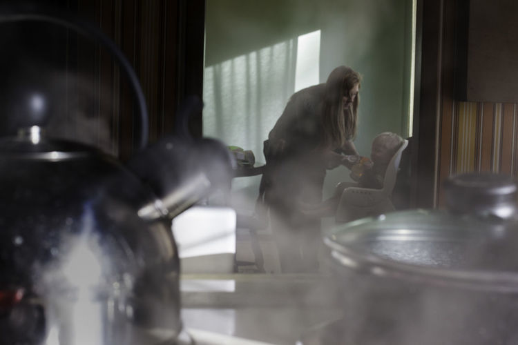 A mother feeds her son breakfast while a kettle of water boils in the foreground. Boling Breakfast Brewing Dining Dining Room Eating Feeding  Indoors  Kettle Kitchen Layers Morning Pajammas People Shadows Steam Water Boiling Always Be Cozy