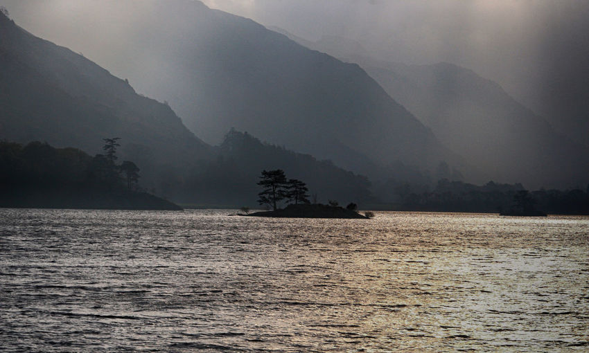 Mist over the mountains viewed from Ullswater lake in the English lake District Beauty In Nature Day Fog Hazy  Island Lake Mist Moist Mood Mountain Mountain Range Mountains Nature No People Outdoors Scenics Sky Tranquility Tree Ullswater, Lake District, Water Waterfront