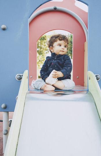 Cute boy sitting on slide at playground