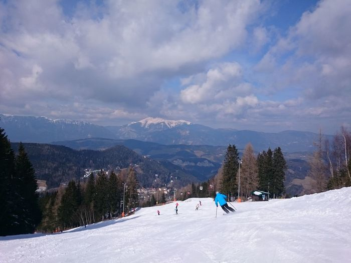 Rear View Of Person Skiing On Snow Covered Field Against Cloudy Sky