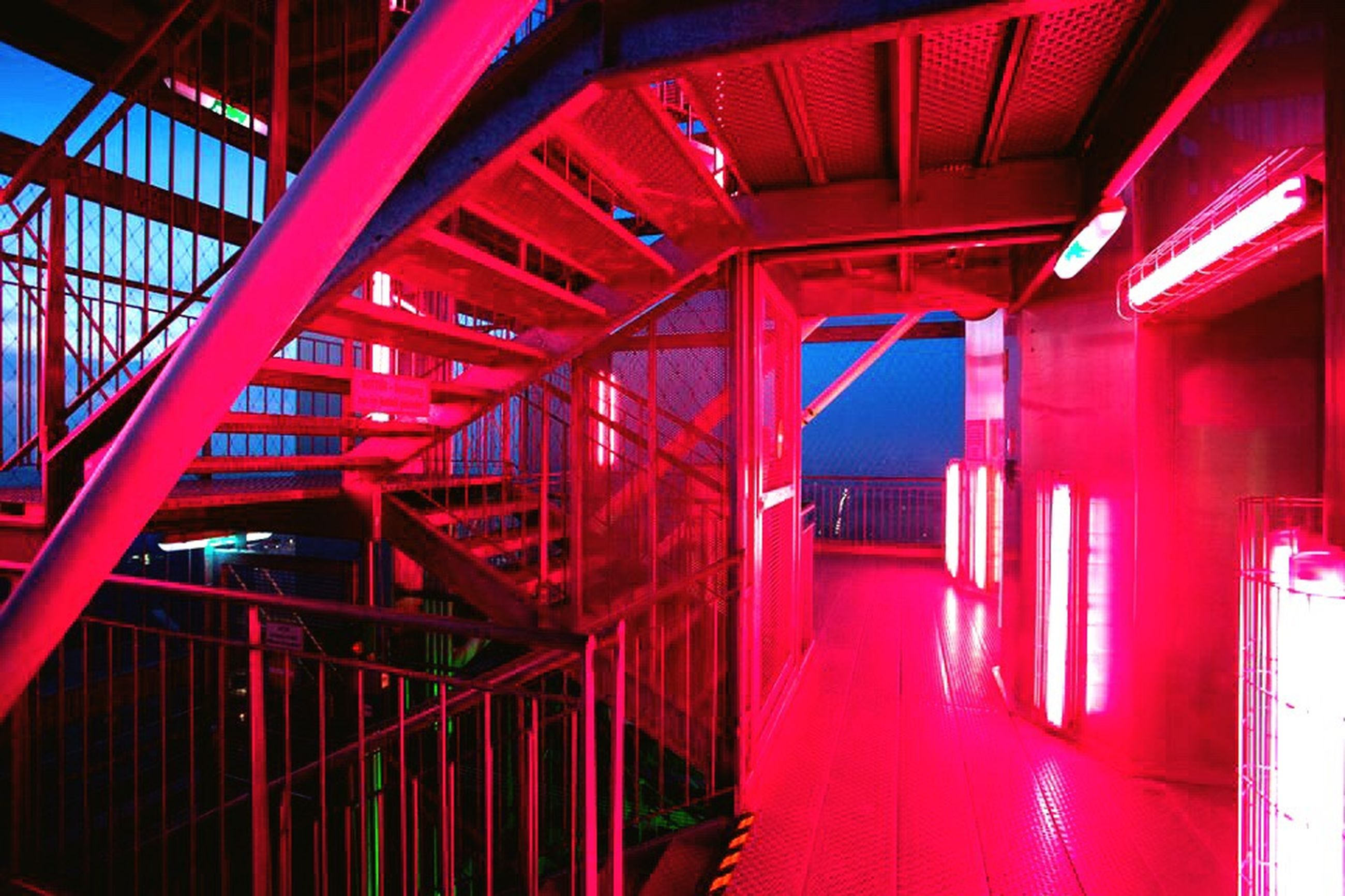 red, indoors, architecture, built structure, illuminated, railing, transportation, steps and staircases, staircase, metal, steps, no people, low angle view, public transportation, night, railroad station, rail transportation, interior, train - vehicle, absence