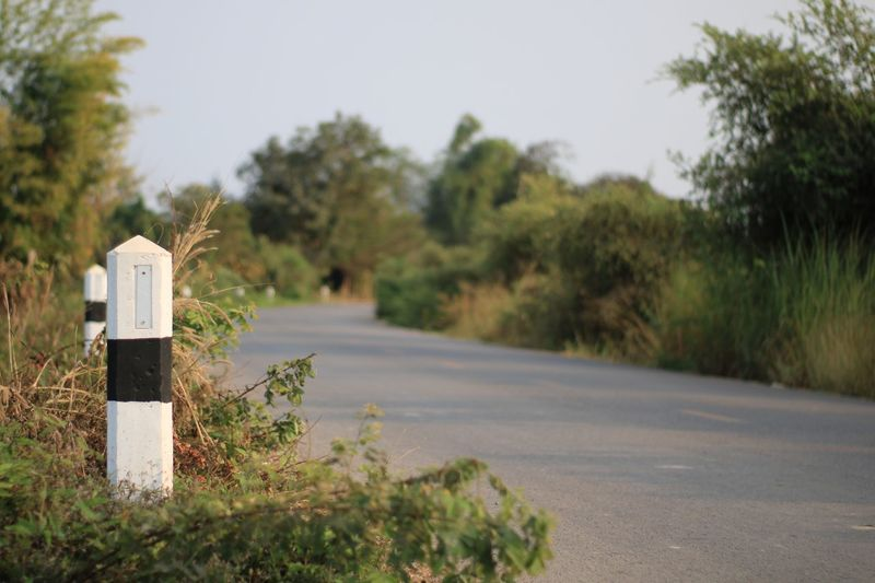 Close-up of kilometer pole by road.