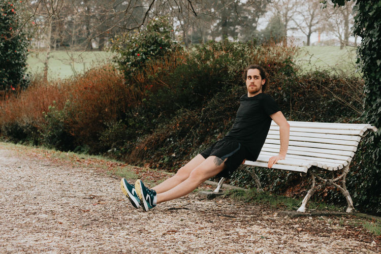 Full length of man exercising by bench