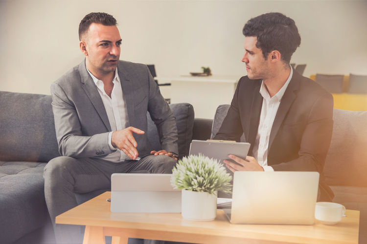 two business people discuss plans for business deals Plan SUPPORT Adult Agreement Business Business Person Businessman Communication Computer Cooperation Cooperation Team Work Deal Furniture Indoors  Job Laptop Males  Men Office Partnership Professional Sitting Startup Success Teamwork
