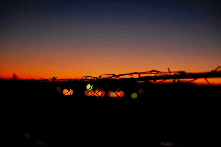 Silhouette of illuminated city against clear sky at sunset