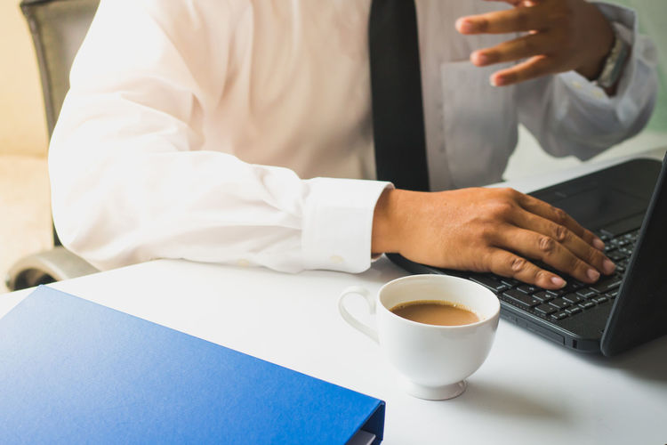 Midsection of businessman using laptop on desk