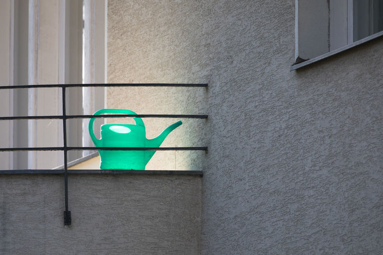 Watering can by railing on balcony