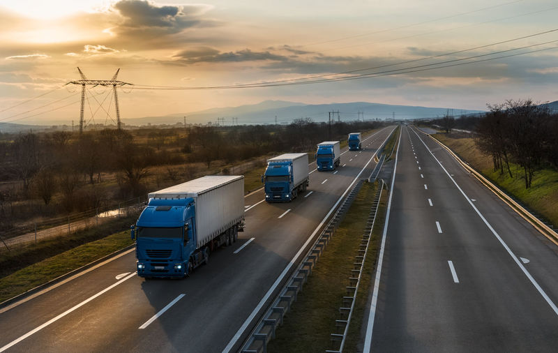 Vehicles on highway against sky