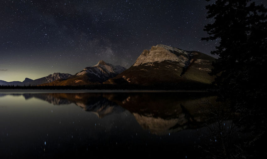 Reflection of mountain in lake against sky at night
