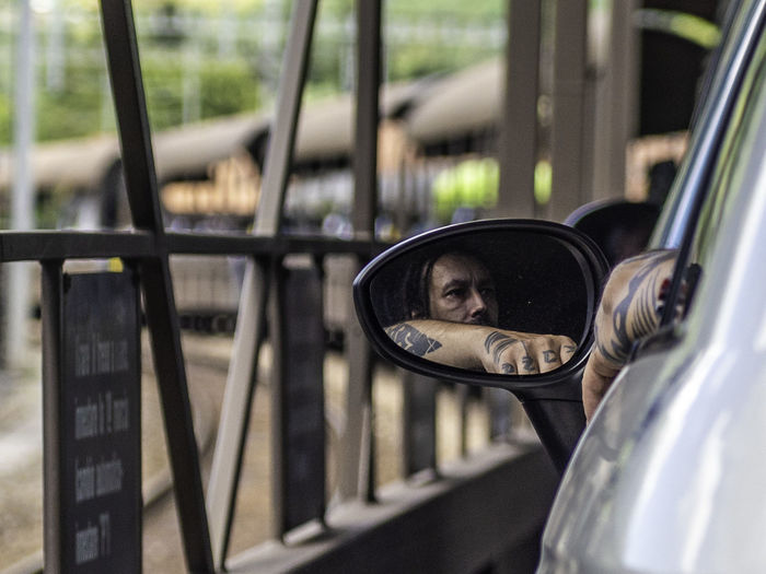 Portrait of man on side-view mirror