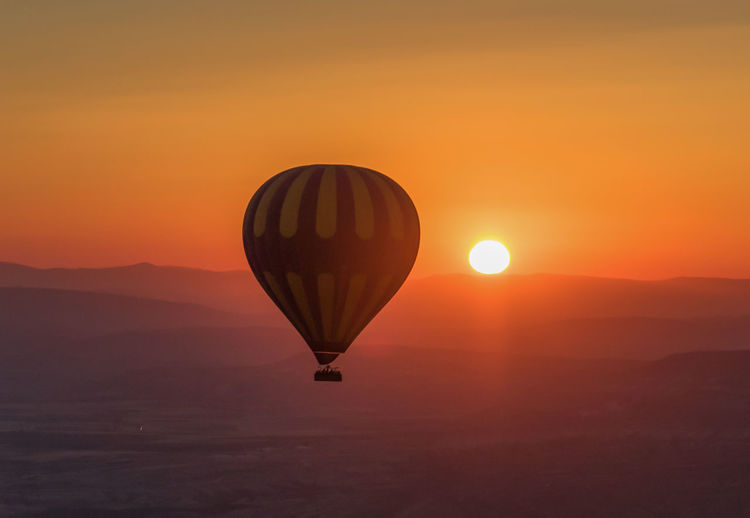Hot air balloon flying against orange sky