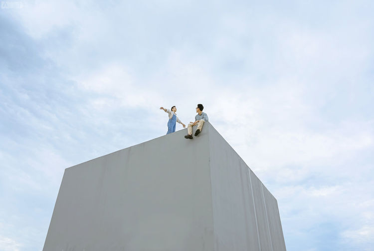 Low angle view of people standing on building against sky