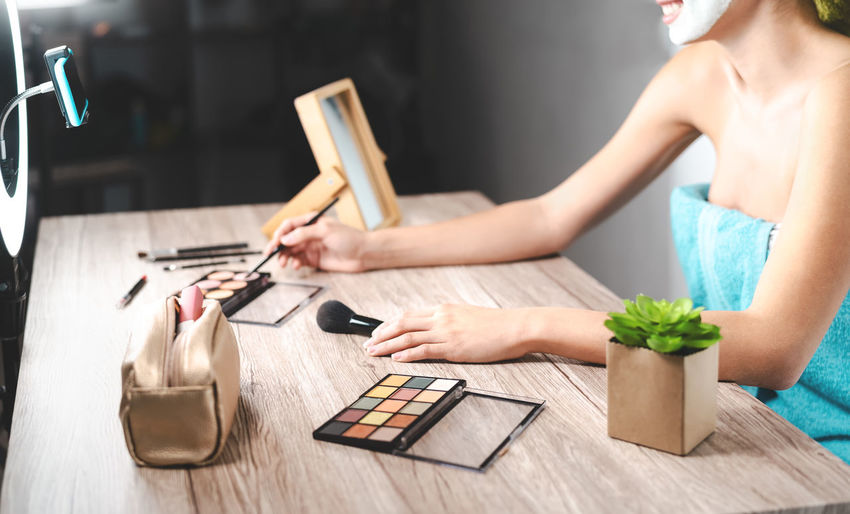 Midsection of woman with beauty products on table blogging at home