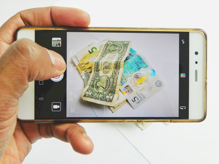 Human Hand Finance Wireless Technology Portable Information Device Mobile Phone Smart Phone Business Finance And Industry Currency Paper Currency Technology Money Around The World Dollar Bill Banknote Taking Photographs Economy Holding Phone Taking Pictures Of Money Light Holding White Background