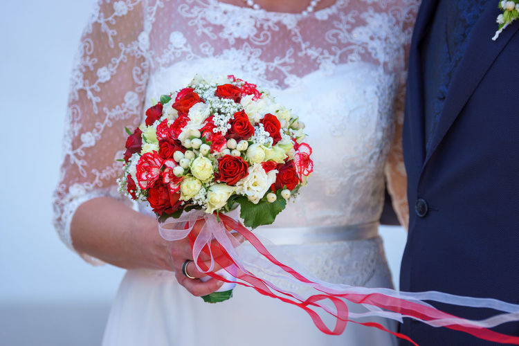 Midsection of woman holding bouquet against red wall