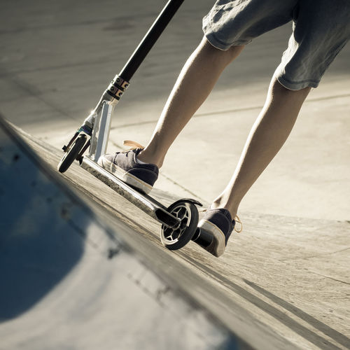 Low section of woman skateboarding on street