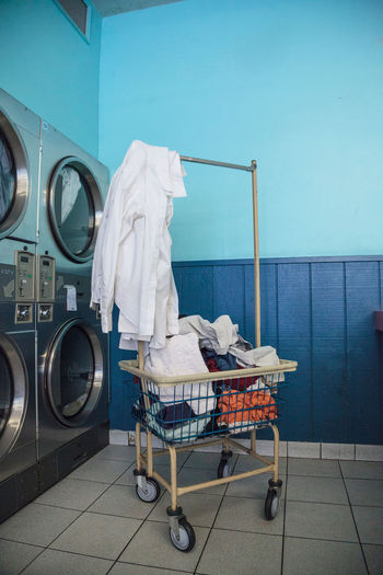 Washing clothes and drying at the Laundromat with chrome washer and dryer units along the isle and walls. Cart Clean Cleans Clothes Day Dryer  Indoors  Laundromat Laundry Machines No People Washing Machine