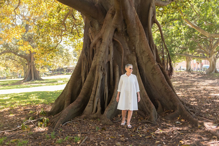 Older woman in white next to large tree Tree One Person Plant Full Length Tree Trunk Trunk Front View Standing Real People Nature Leisure Activity Lifestyles Day Land Casual Clothing Growth Portrait Outdoors WoodLand Hairstyle Senior Women Women