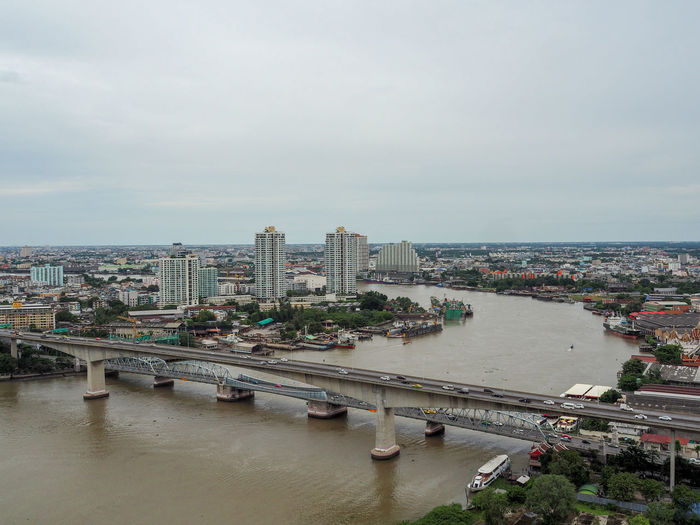 High angle view of bridge over river by buildings in city against sky