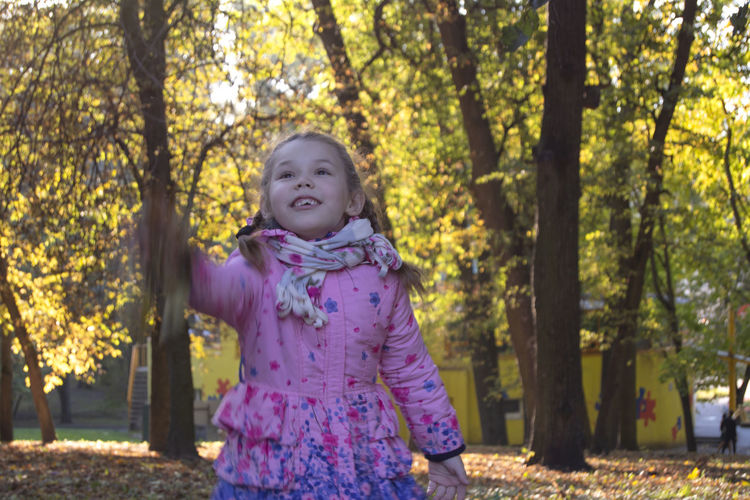 Emotions Happiness Autumn Portrait Casual Clothing Child Childhood Cute Females Front View Girls Hairstyle Innocence Leisure Activity Looking At Camera One Person Outdoors Pink Color Plant Portrait Real People Standing Three Quarter Length Tree Women